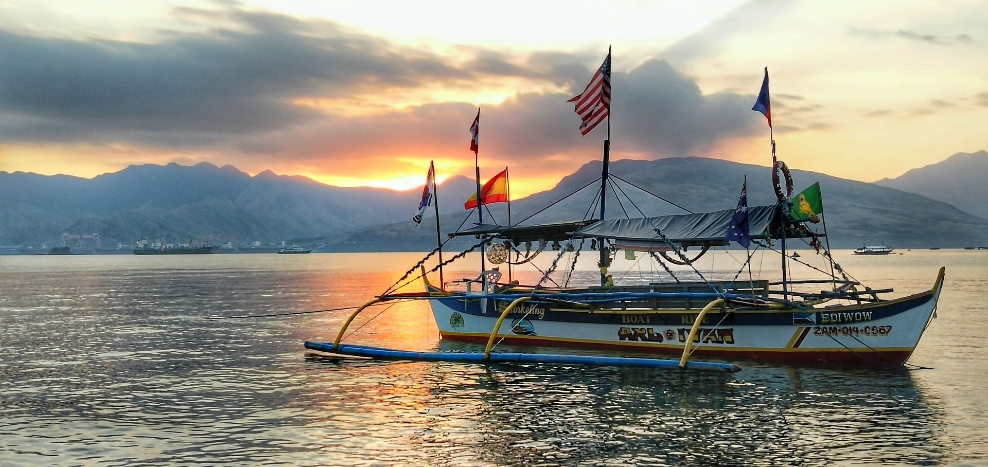 Image of a boat with country flags flying on the water in the Philippines