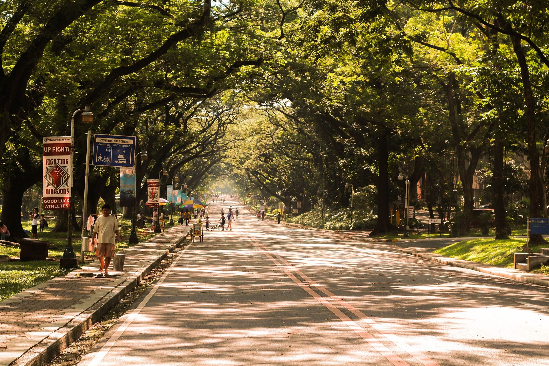 Pedestrians walk along a tree-lined street in Manila in the Philippines.